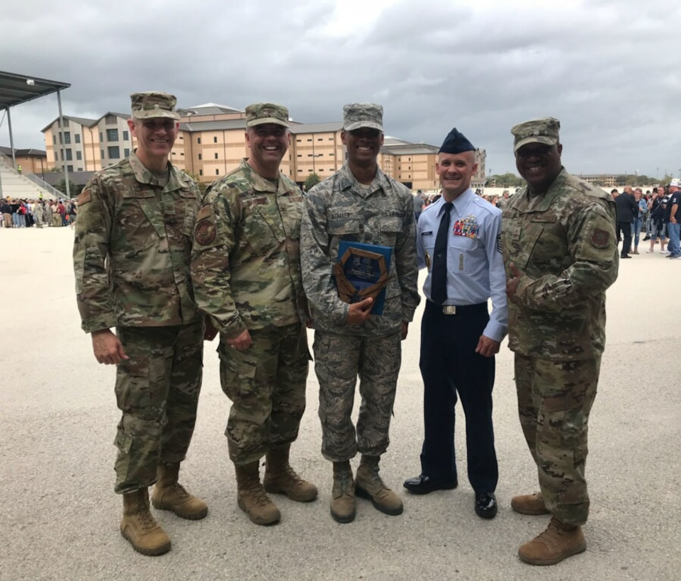 Airman 1st Class Ronald Straker, center, an Airman with the 118th Wing, Tennessee Air National Guard, poses with his recruiter and leadership at basic military training graduation Oct. 25, 2019 at Lackland Air Force Base, San Antonio, Texas.