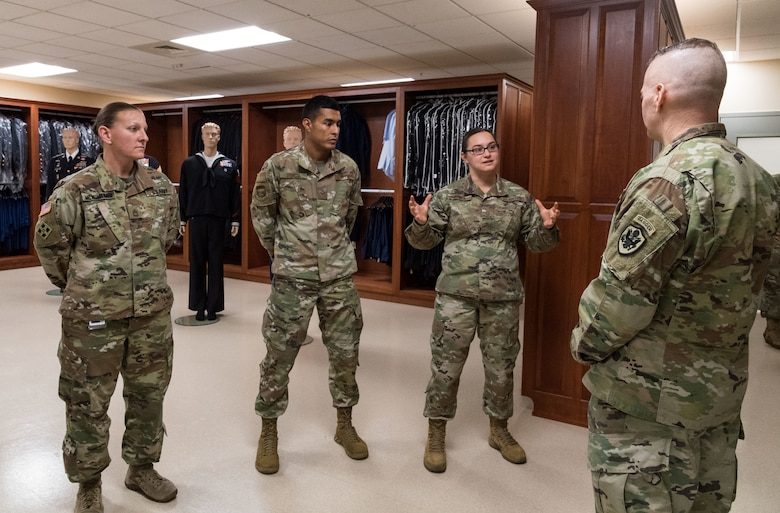 Master Sgt. Naomi Bouska, Air Force Mortuary Affairs Operations  noncommissioned officer in charge of uniforms, briefs Army Command Sgt. Maj. John Wayne Troxell, senior enlisted advisor to the chairman of the Joint Chiefs of Staff, Dec. 3, 2019, during an orientation of the mortuary facility. Troxell thanked Bouska, Sgt. 1st Class Nicole McMinamin and Senior Airman Isai Sorcia for their service in providing dignity, honor and respect to fallen service members. (U.S. Air Force photo by Roland Balik)