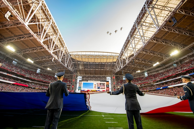 Airmen hold a giant American flag on a football field as four aircraft fly over the stadium.