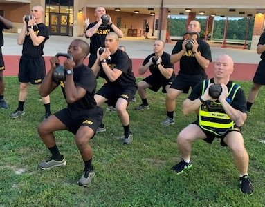 Maj. Edward Jarrett, U.S. Army Engineer School executive officer, right, performs goblet squats with trainees assigned to Company D, 31st Engineer Battalion. The company is piloting a new concept in physical readiness called the Strength Training Program, which is designed to reduce injuries throughout Basic Combat Training