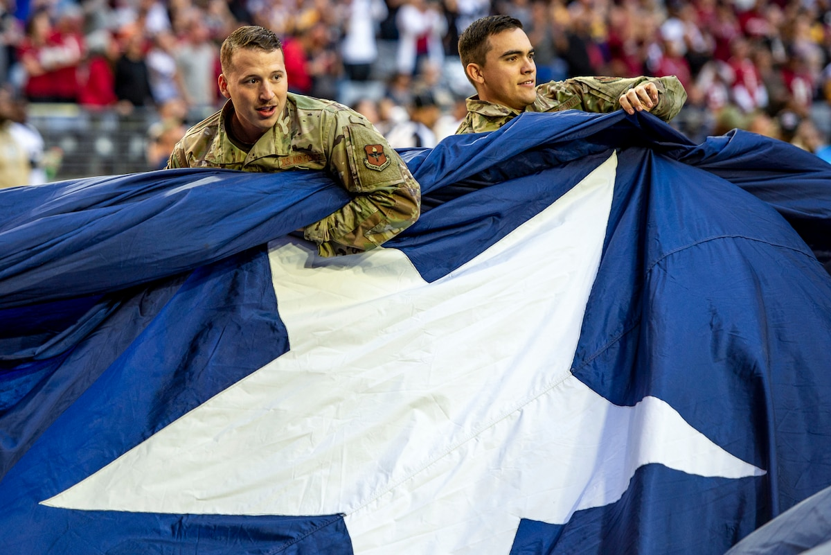 Two airmen standing on a field in a stadium hold up a blue section of a giant U.S. flag with a white star.