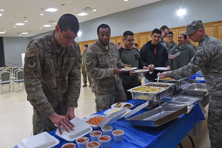Airmen stand in line for food