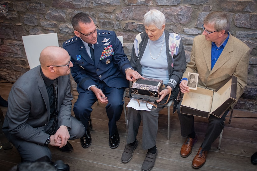 Three men and a woman sit in chairs as they look at an accordion found during World War II. One of the men holds a photo of a soldier above an album that is in his lap.