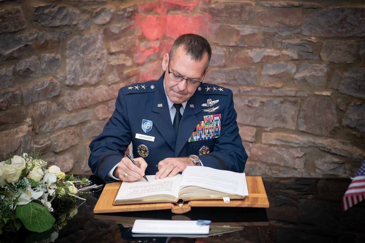 Air Force three-star general signs a book while seated at a table.