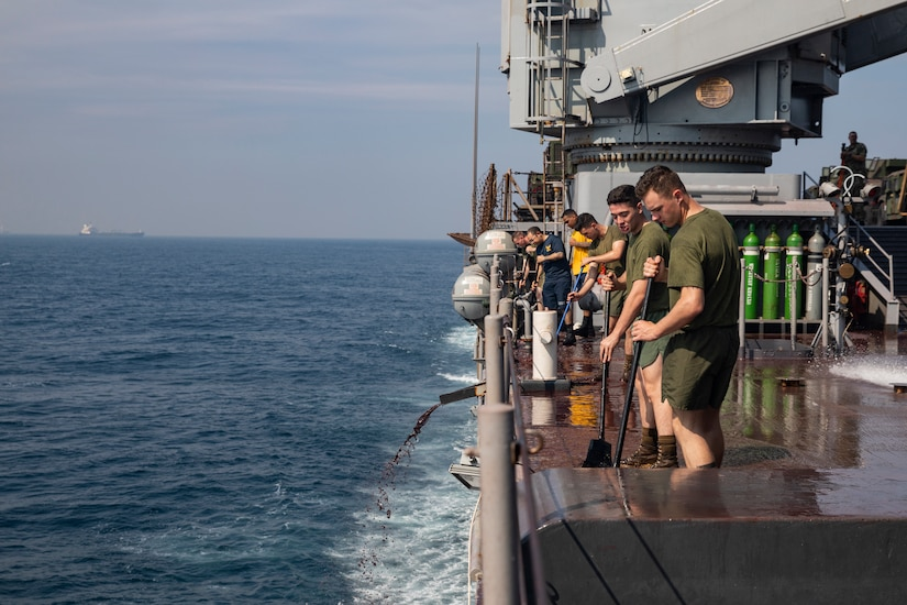 A group of marines and sailors sweep a warship.