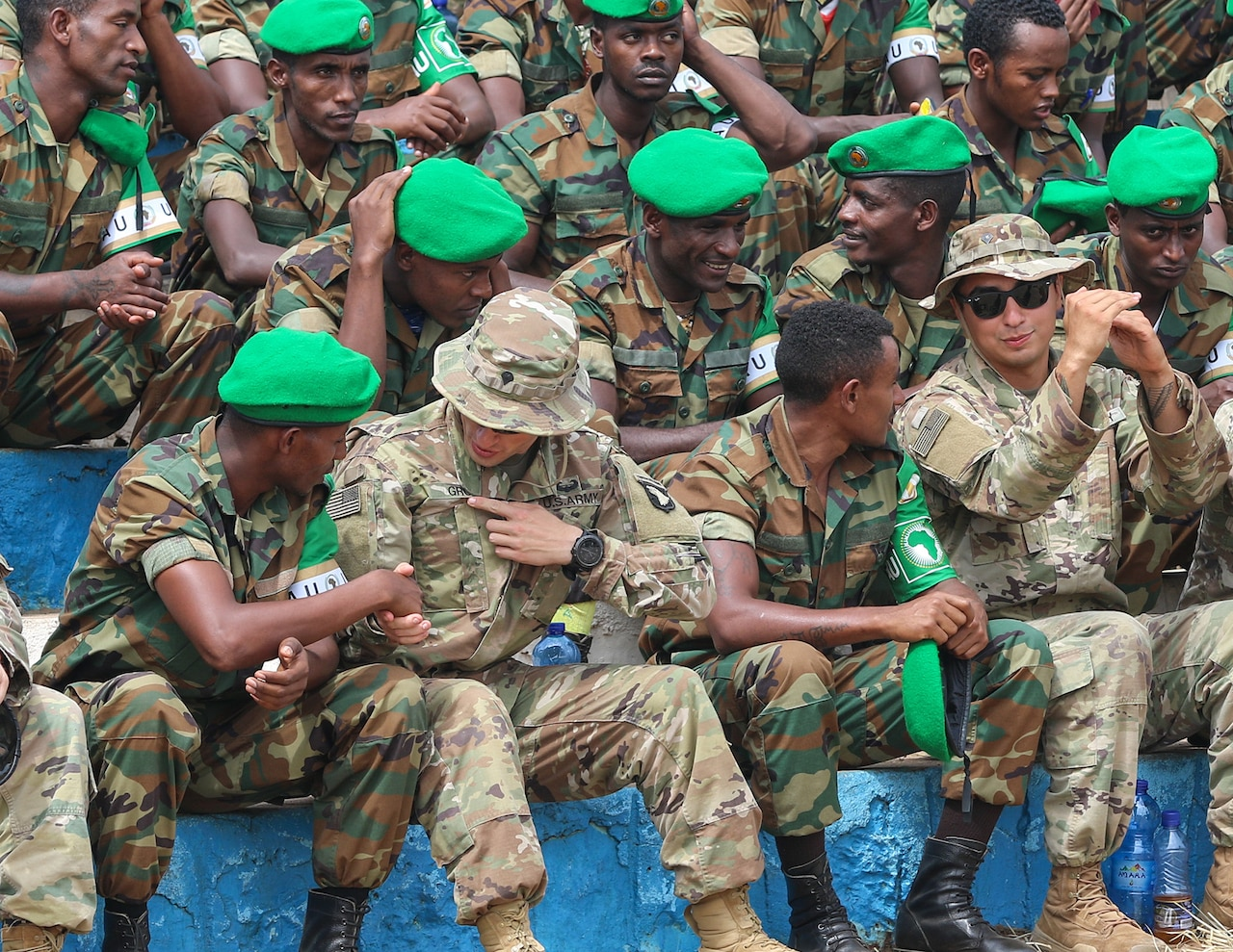 Soldiers in camouflage uniforms, some wearing bright green berets, talk while sitting in bleachers.