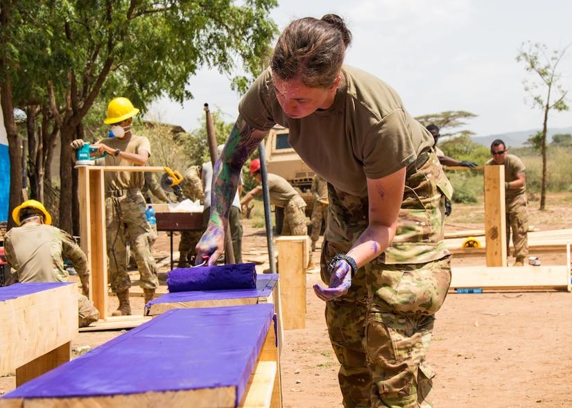 A soldier paints a desktop purple.
