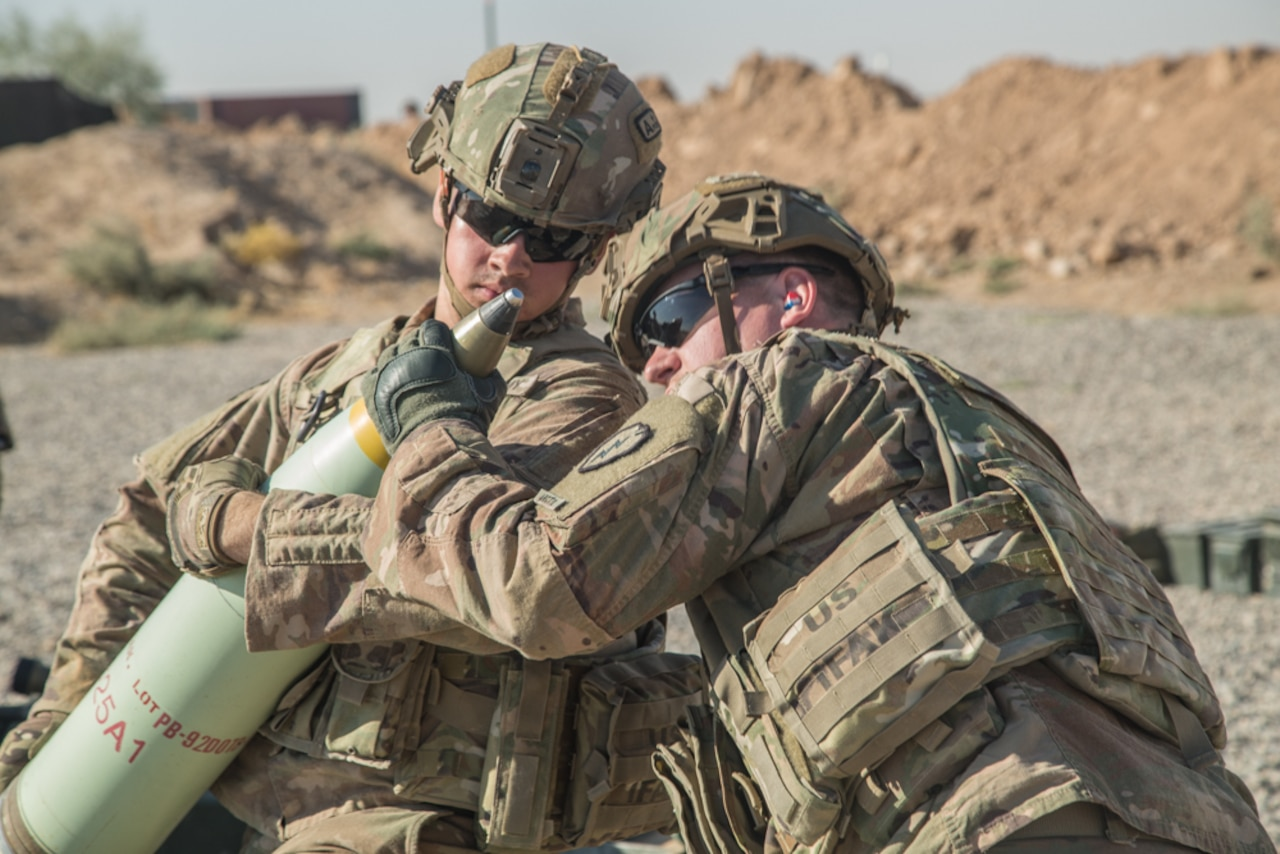 Two soldiers handle an artillery shell.