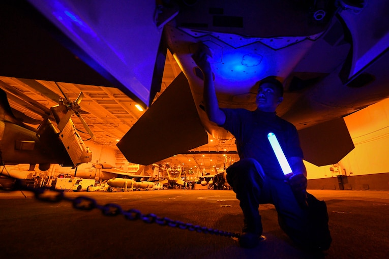 A sailor kneels under an aircraft while holding a blue light.