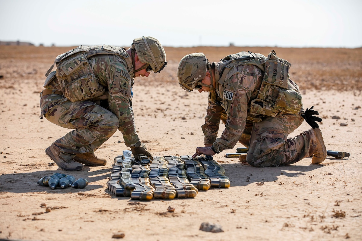 Two soldiers align ammunition on the ground.
