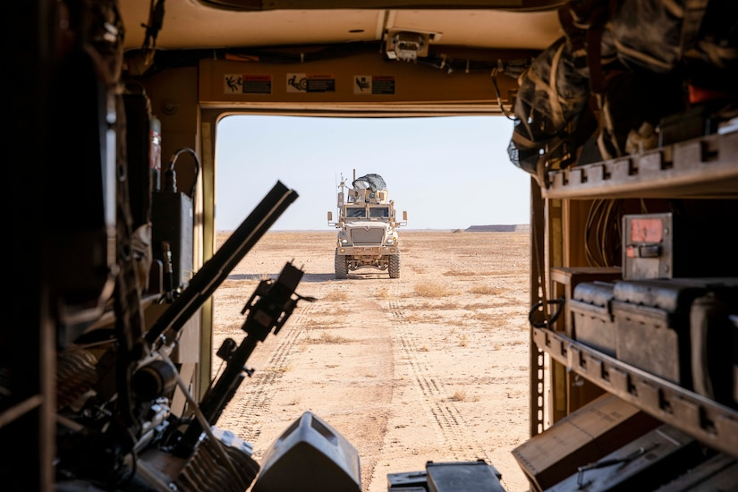 A military vehicle drives through dirt.