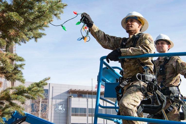 Two airmen put Christmas lights on a tree.