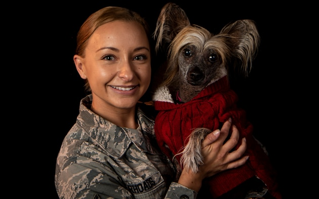 An Airman holds a therapy dog.