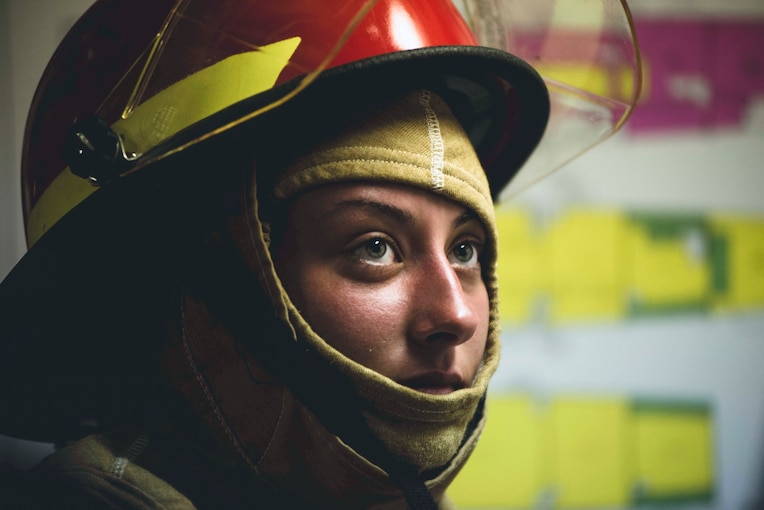 A Coast Guardsman wearing a firefighting helmet looks at something aboard a ship.