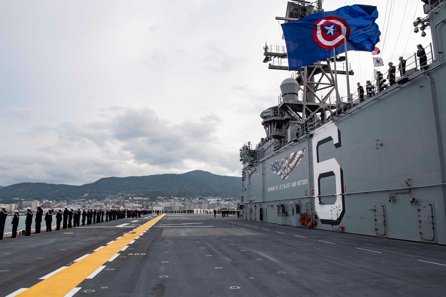 SASEBO, Japan (Dec. 6, 2019) Sailors man the rails as the amphibious assault ship USS America (LHA 6) arrives at Sasebo, Japan to join the forward-deployed naval forces. America is assigned to Amphibious Squadron Eleven and will serve as the flagship for Expeditionary Strike Group 7 while conducting routine operations in the Western Pacific.