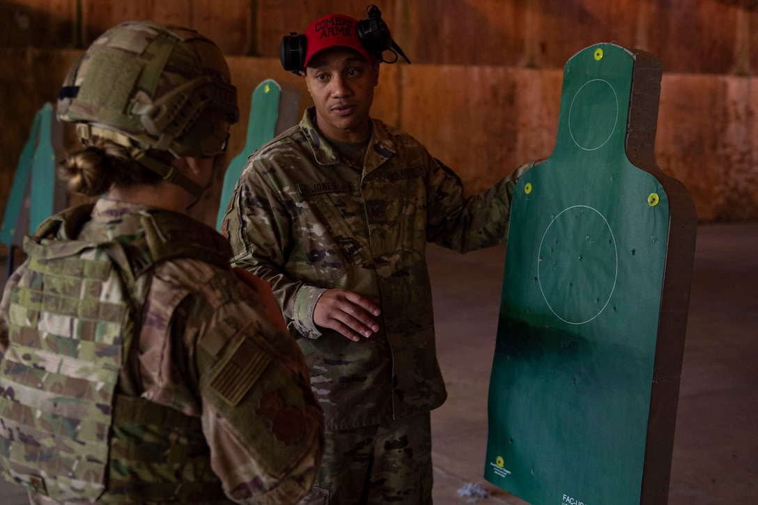 Photo of a combat arms instructor analyzing an Airman's target during an M4 and M9 Air Force Qualification Course
