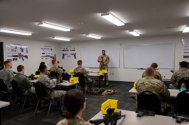 Photo of a combat arms instructor teaching an M4 and M9 Air Force Qualification Course