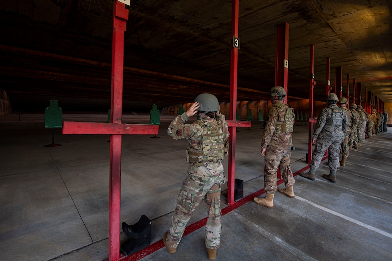 Photo of Airmen in an M4 and M9 Air Force Qualification Course preparing to fire weapons