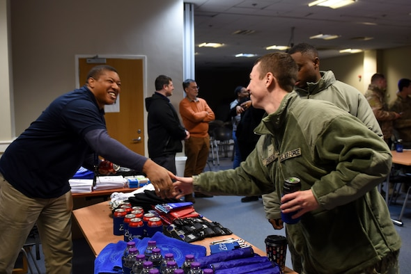 A volunteer greets Liberty Wing Airmen at the first ever Mid-Shift Chili Fest event at Royal Air Force Lakenheath, England, Dec. 5, 2019. The event consisted of a variety of chili, cookies, apple cider, an array of games, and merchandise from different helping agencies from across the Liberty Wing. (U.S. Air Force photo by Airman 1st Class Rhonda Smith)