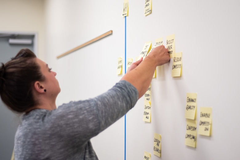 Jessica Winningham, an interior designer and participant of a three-day value engineering workshop for the Furnishings Program, adjusts sticky notes during the workshop's Creative Phase at the U.S. Army Engineering and Support Center, Huntsville, Alabama, Nov. 4, 2019.