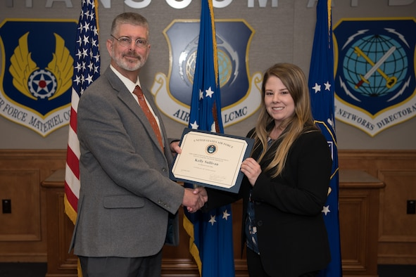 Kelly Sullivan, a PALACE Acquire graduate and program manager for the Digital Directorate, receives a certificate from Scott Owens, deputy director of Command, Control, Communications, Intelligence and Networks, during a graduation ceremony for program management trainees at Hanscom Air Force Base, Mass., Dec. 5.