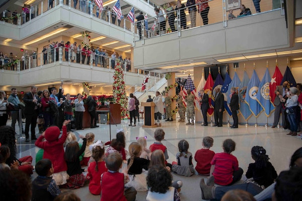 Santa Claus walks down stairs as HQC CDC children wave and HQC employees look on during the HQC annual tree lighting ceremony.
