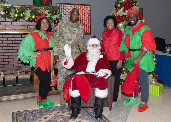 """Two women and two men pose with """"Santa Claus"""" during  the annual HQC holiday social Dec. 5."""