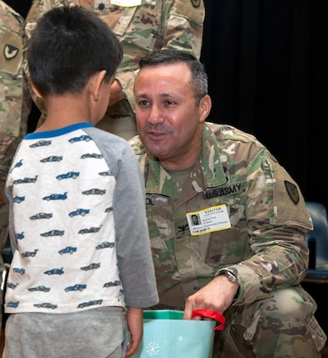 Col. Samuel E. Fiol, 502nd Force Support Group commander, presents a gift bag to a student at Wilshire Elementary School in San Antonio Dec. 4 as part of the Adopt a School program. The school is a Title I Campus with 88 percent of students identified as economically disadvantaged.