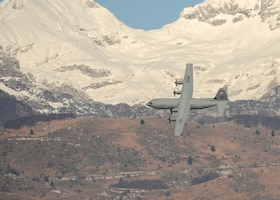 A C-130J Super Hercules flies across the Italian Dolomites