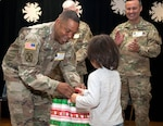 Sgt. Maj. Danang McKay, 502nd Force Support Group command sergeant major, gives a personalized gift bag to a student at Wilshire Elementary School in San Antonio Dec. 4 as part of the Adopt a School program. To help ensure the students at the school are warm during the winter months, 502nd FSG volunteers collected coats, socks, and toys to give needy children as part of the program.
