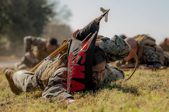 Sgt. Lynarae Pena, a tactical switching operator with Reserve Base Support, Marine Forces Reserve, low crawls to the objective while carrying the guidon during Martial Arts Instructor Course 1-20 aboard Naval Air Station Joint Reserve Base New Orleans, Dec. 4, 2019. The course consists of both physical and mental challenges to mold Martial Arts Instructors. (U.S. Marine Corps photo by Pfc. Colby Bundy)