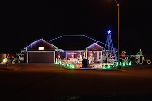 Military family displays holiday lights.