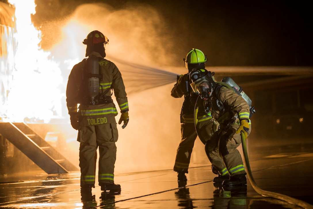 U.S. Marines with Aircraft Rescue and Firefighting, Headquarters and Headquarters Squadron, Marine Corps Air Station Yuma conduct low light hand line drills during live burn training on MCAS Yuma, Ariz., Nov. 21, 2019. Hand line drills focus on techniques to push fuel fires away from aircraft, ARFF Marines train monthly to enhance their readiness when responding to emergencies on the flight line.