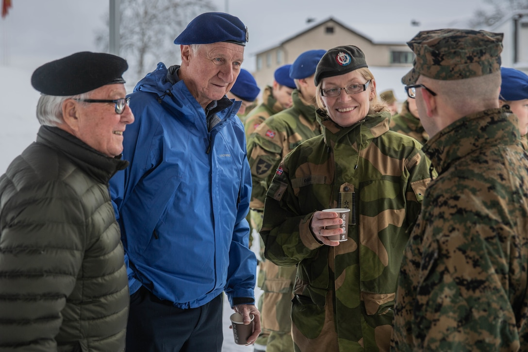 Norwegian Soldier and Norwegian Veterans talk to a U.S. Marine with Marine Rotational Force-Europe 20.1, Marine Forces Europe and Africa, during Veterans Memorial Day Ceremony in Bardufoss, Norway, Nov. 1, 2019. MRF-E focuses on regional engagements throughout Europe by conducting various exercises, arctic cold-weather and mountain-warfare training, and military-to-military engagements, which enhance overall interoperability of the U.S. Marine Corps with allies and partners.