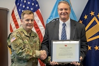 On behalf of Ryan D. McCarthy, Secretary of the U.S. Army, Brig. Gen. Mark S. Bennett, U.S. Army Financial Management Command commanding general, presents Greg Schmalfeldt, Defense Finance and Accounting Service Indianapolis director, with an Army Excellence in Financial Stewardship Award for Fiscal Year 2019 at the Maj. Gen. Emmett J. Bean Federal Center in Indianapolis Dec. 3, 2019. Immediately upon joining the Command Accountability and Execution Review program, the Army's fiscal stewardship program that provides commanders with visibility of command fiscal health and holds leaders at every echelon responsible and accountable for stewardship of the tax dollars, Schmalfeldt demonstrated strong leadership, and his solutions provided to the program immediately reduced manual workload on transportation billing by 75 percent and freed up approximately $170 million in funding for use on other priorities. (U.S. Army photo by Mark R. W. Orders-Woempner)