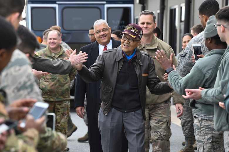 Former Tuskegee Airman, retired Col. Charles McGee, high-fives Airmen during his visit Dec. 6, 2019, at Dover Air Force Base, Del. He served a total of 30 years in the U.S. Air Force, beginning with the U.S. Army Air Corps, and flew a total of 409 combat missions in World War II, Korea and Vietnam. The Tuskegee program began in 1941 when the 99th Pursuit Squadron was established, and its Airmen were the first ever African-American military aviators in the U.S. Army Air Corps. (U.S. Air Force photo by Senior Airman Christopher Quail)