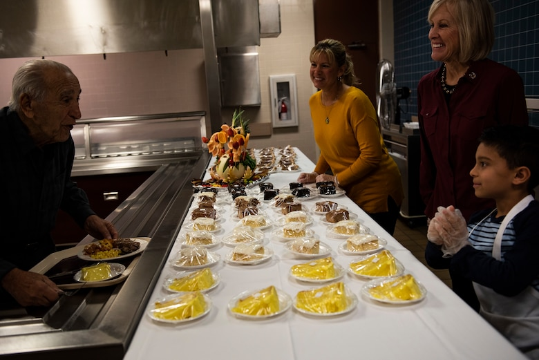 Retired U.S. Air Force Lt. Col. Daniel Daube, left, is served a dessert by Samantha Laidlaw, center, and Leah Dunn, right, at the 325th Force Support Squadron dining facility at Tyndall Air Force Base, Florida, Nov. 28, 2019. Attendees of the holiday meal celebration were served food by commanders, chiefs, first sergeants, and special guests of the 325th Fighter Wing. (U.S. Air Force photo by Staff Sgt. Magen M. Reeves)