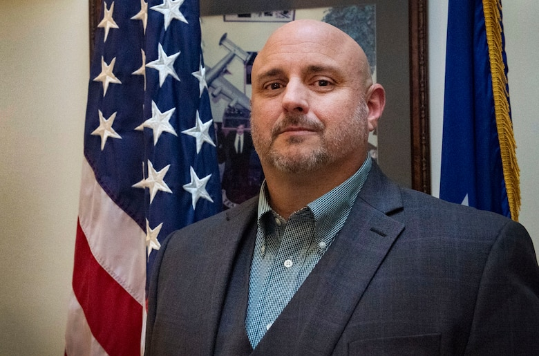 Rob Schenk, 66th Logistics Readiness Squadron and installation deployment officer, poses for a photo outside his office in the Brown Building on Hanscom Air Force Base, Dec. 4. As the IDO, Schenk is responsible for the rotation of deplopying service members and civilians throughout the New England and parts of New York. (U.S. Air Force photo by Lauren Russell)
