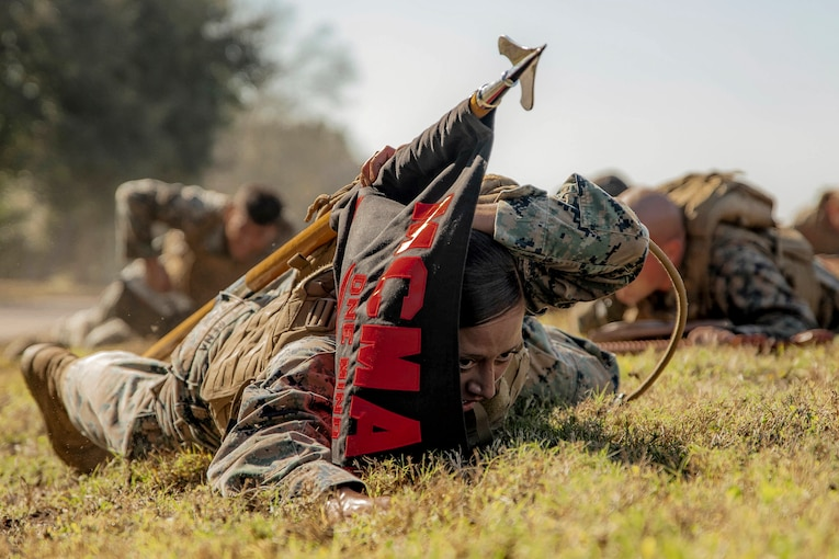 A Marine crawls on the ground while carrying a guidon.