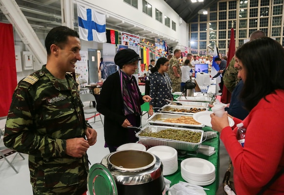 A military representative to U.S. Central Command's (USCENTCOM) Coalition from Morocco serves native cuisine to guests at USCENTCOM's 16th annual Coalition International Night in Hangar 5 at MacDill Air Force Base (AFB), Dec. 5, 2019. International Night started in December 2004 as a winter holiday party for the Coalition members and families. This year, members of 37 coalition countries displayed native customs and offered a taste of their traditional cuisines to over 1,700 guests. (U.S. Central Command Public Affairs photo by Tom Gagnier)