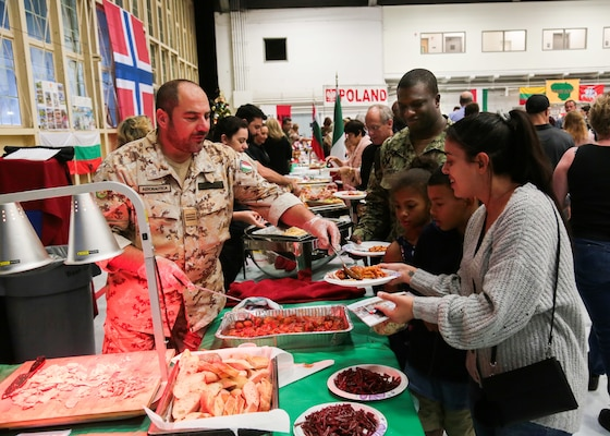 A military representative to U.S. Central Command's (USCENTCOM) Coalition from Italy serves native cuisine to guests at USCENTCOM's 16th annual Coalition International Night in Hangar 5 at MacDill Air Force Base (AFB), Dec. 5, 2019. International Night started in December 2004 as a winter holiday party for the Coalition members and families. This year, members of 37 coalition countries displayed native customs and offered a taste of their traditional cuisines to over 1,700 guests. (U.S. Central Command Public Affairs photo by Tom Gagnier)