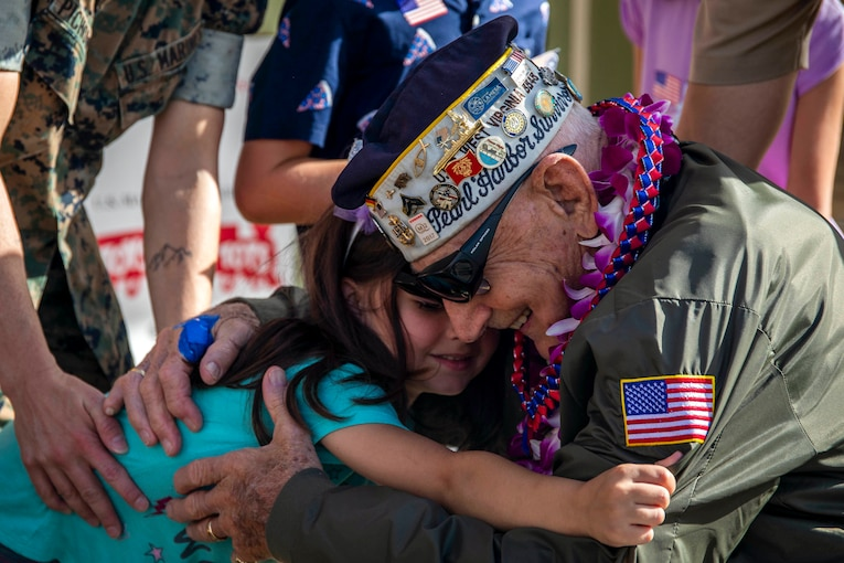 A veteran and a little girl hug, both smiling.