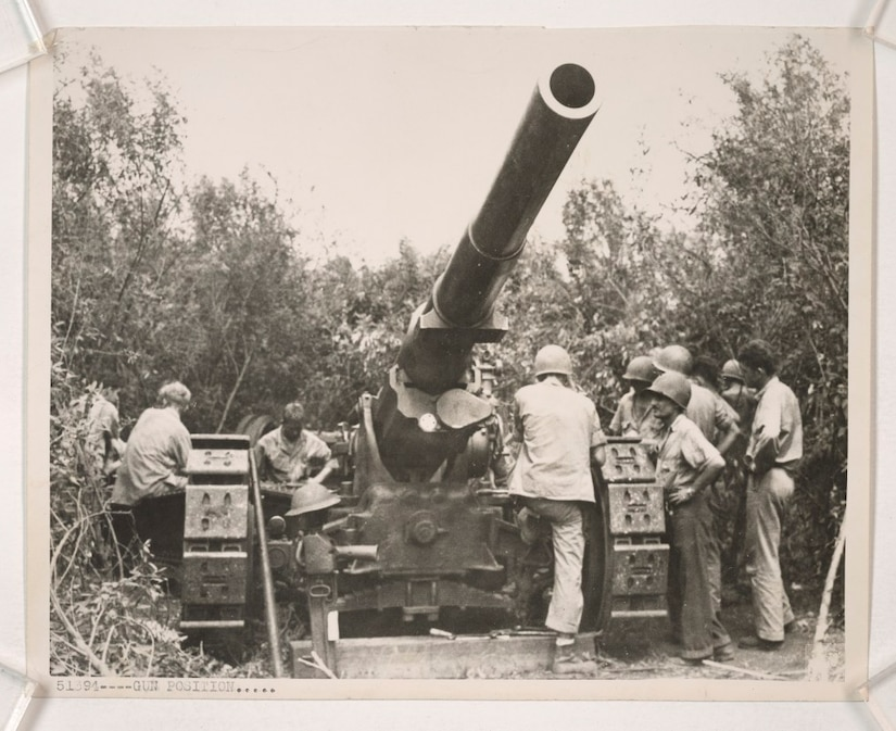 A handful of Marines work on a massive 155 mm gun surrounded by jungle