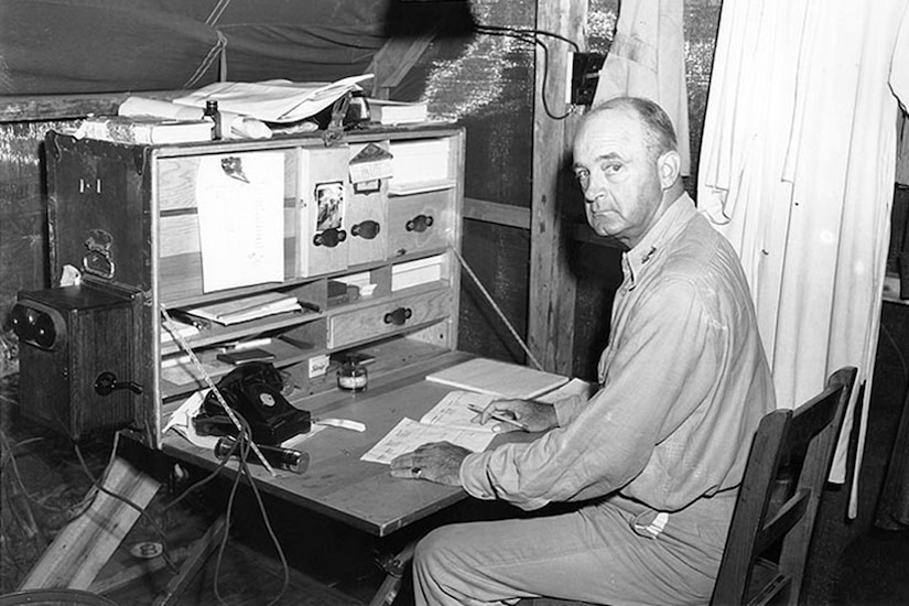An older Marine looks over his shoulder at the camera as he sits at a work station in a tent.