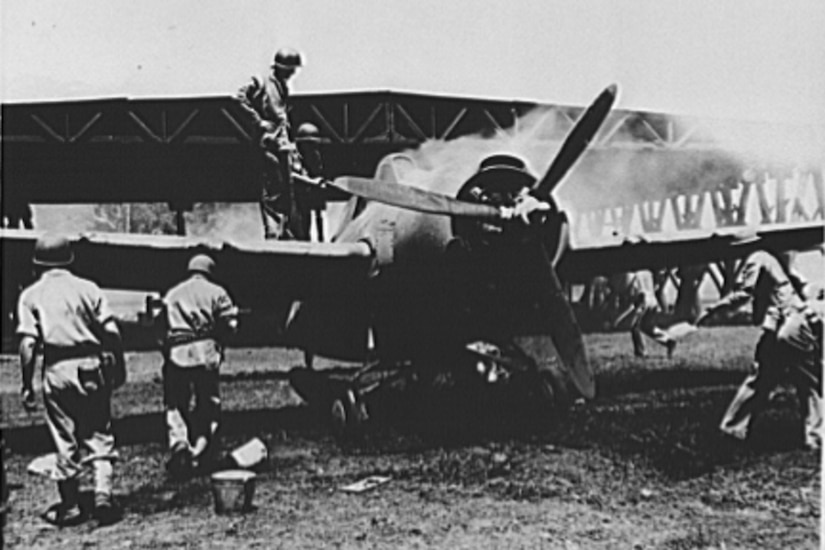 Marines on the ground put out a propeller airplane fire as two men stand on its wing to take a look. A hangar is in the background.
