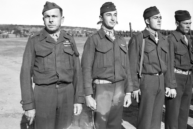 Four Marines stand in a row on what appears to be an airfield. The two men in the middle are wearing Medals of Honor.