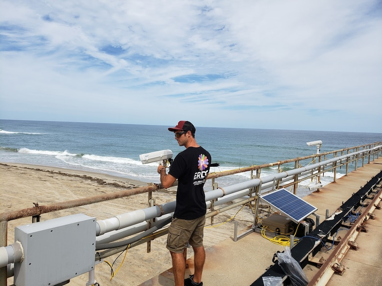 Nicholas Spore, a research civil engineer with the U.S. Army Engineer Research and Development Center's Coastal and Hydraulics Laboratory's Field Research Facility, positions equipment along a pier in Duck, North Carolina, Sept. 4, 2019, as part of the During Nearshore Event Experiment pilot study now underway along the Outer Banks. DUNEX is a multi-agency, academic and non-governmental organization collaborative community experiment to study nearshore coastal processes during coastal storms.