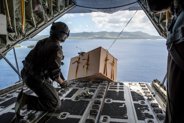 An airman drops a box from the back of an open aircraft.