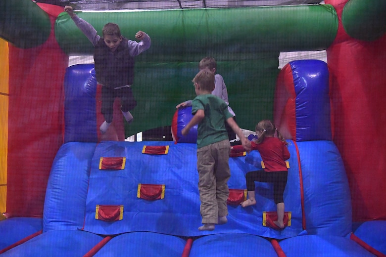 Children play in a bouncy house during the Red-Nosed Herk holiday celebration.