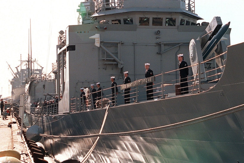 Several sailors in dress blues stand at the rail of a large, docked guided missile frigate. In small letters you can see the ship's name, USS Vandegrift FFG 48.
